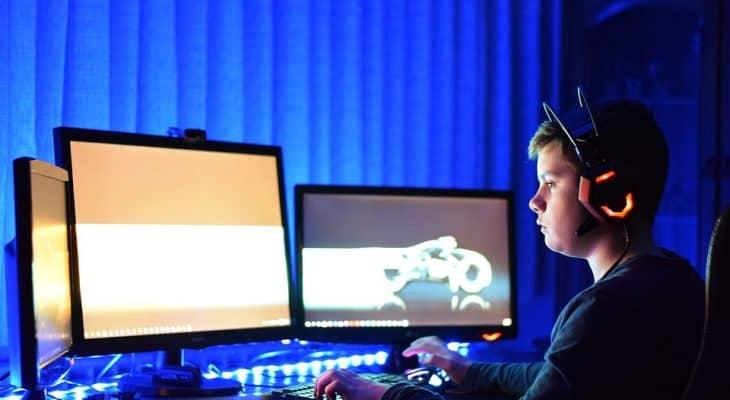 young-gamer-looking-at-3-monitors